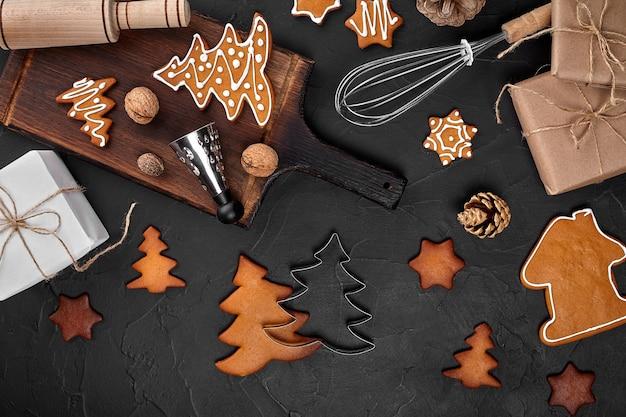 Spezie e tagliere casalinghi dei biscotti del pan di zenzero di natale su fondo scuro con lo spazio della copia f...