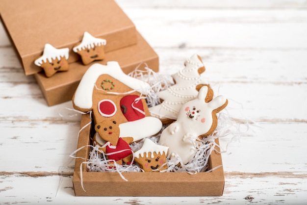 Biscotti di pan di zenzero fatti in casa di natale sulla tavola di legno. regalo di capodanno in scatola, sorpresa bianca