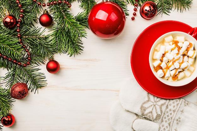 Bevanda calda di natale in tazza rossa cacao con cannella al cioccolato marshmallow e decorazioni natalizie su una vista superiore del fondo di legno