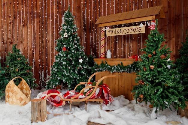 Interno natalizio del soggiorno con albero di natale e slitta a buffet con scritta milk amp cookies