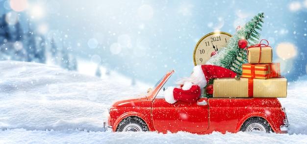 Natale sta arrivando. babbo natale in una macchinina rossa che consegna un regalo per il capodanno 2021 e l'orologio di capodanno sul paesaggio invernale della neve