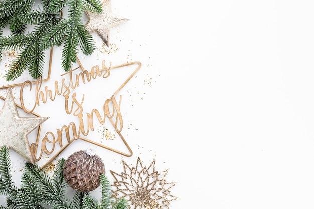 Il natale sta arrivando scritto vicino alle decorazioni natalizie