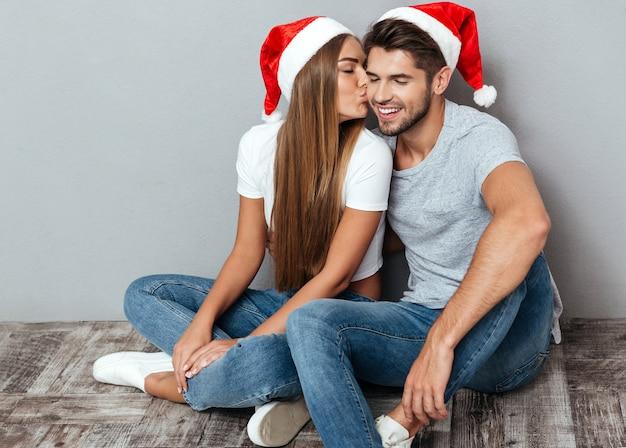 Natale che si bacia coppia seduta