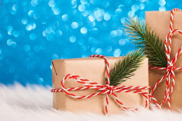 Contenitore di regalo kraft di natale sulla superficie scintillante blu