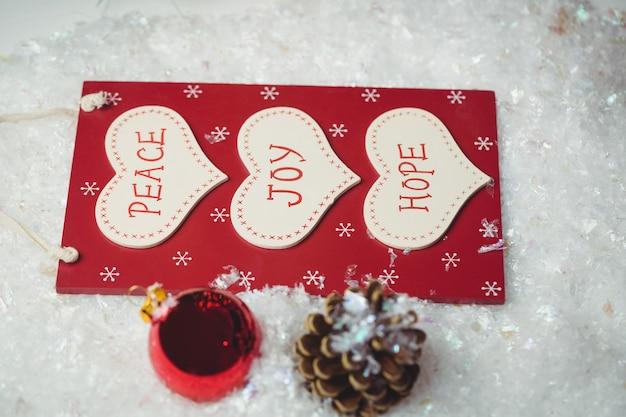 Contrassegno di natale con i messaggi e gli ornamenti di natale su neve