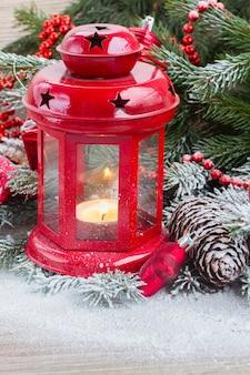 Lanterna di natale da vicino con albero sempreverde e neve