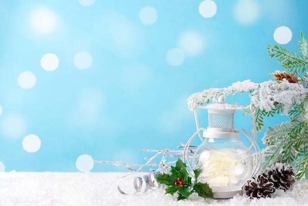 Lanterna di natale sulla neve con ramo di abete e decorazioni invernali sull'azzurro. concetto di vacanza di natale.
