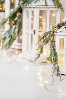 Lanterne di natale e rami di abete innevati su legno bianco