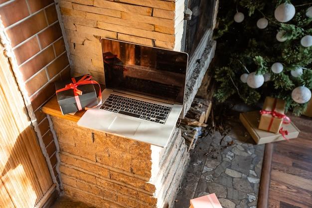 Computer portatile di natale con albero di natale in una vecchia casa di legno
