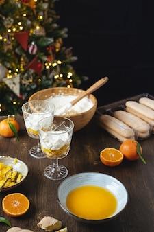 Dessert natalizio a strati, cheesecake senza cottura o zuppa inglese con mandarini e cioccolato