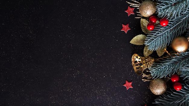Layout di natale con albero di pino, palline d'oro e campane, stelle rosse su sfondo nero con spazio di copia. composizione vista dall'alto