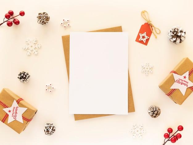 Lettera di natale per babbo natale con cartolina vuota e decorazioni di natale sulla tavola bianca