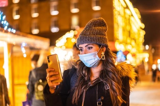 Stile di vita natalizio in una nuova normalità. ragazza con maschera facciale in visita al mercatino di natale guardando il cellulare nella pandemia di coronavirus, covid-19