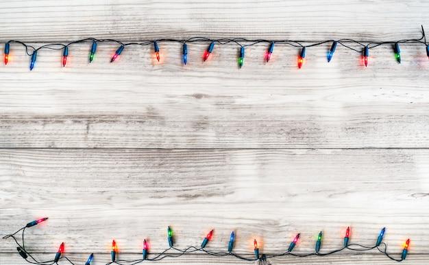 Decorazione della lampadina delle luci di natale sulla plancia di legno bianca. fondo di festa di buon natale e capodanno. tonalità di colore vintage.
