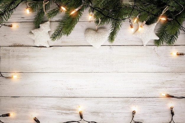 Lampadina delle luci di natale e decorazione delle foglie di pino sulla plancia di legno bianca