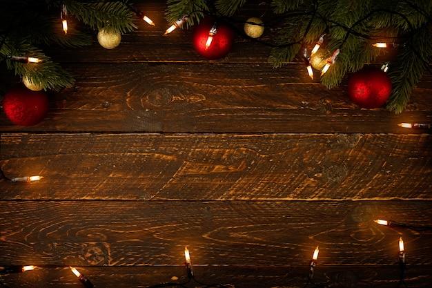 Lampadina delle luci di natale e decorazione delle foglie di pino sulla plancia di legno