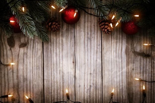 Lampadina delle luci di natale e decorazione delle foglie di pino sulla tavola di legno