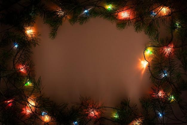 Cornice di luci di natale su sfondo scuro. vista dall'alto del bordo della ghirlanda brillante delle vacanze. decorazioni per l'albero di natale, illuminazione per le vacanze invernali