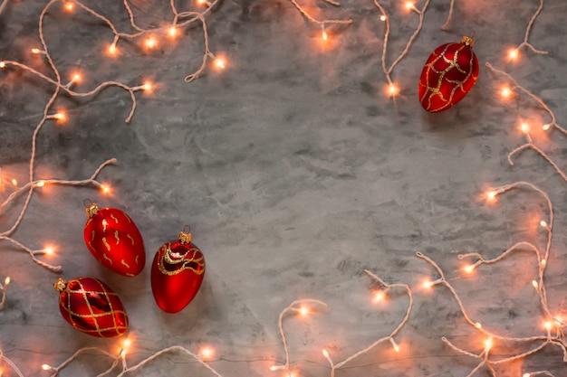 Le luci di natale incorniciano su fondo di pietra scuro con gli ornamenti rossi