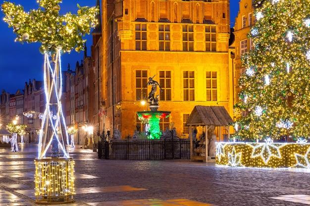 Mercatino di natale lungo la strada con la fontana del nettuno di notte nel centro storico di danzica