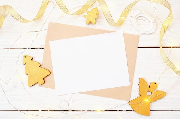 Posta di natale su uno sfondo di legno bianco con un angelo d'oro e un albero di natale. mockup di foto vista dall'alto piatto.