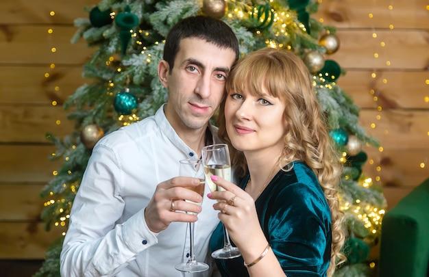 Uomo e donna di natale con bicchieri di champagne. messa a fuoco selettiva. vacanza.