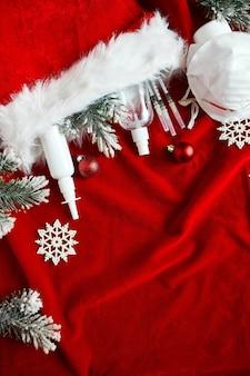Piatto di coronavirus medico di natale, maschera protettiva, pillole, antisettici, decorazione su sfondo rosso, tema del nuovo anno vista dall'alto, minimalismo, layout piatto, concetto di covid e felice anno nuovo