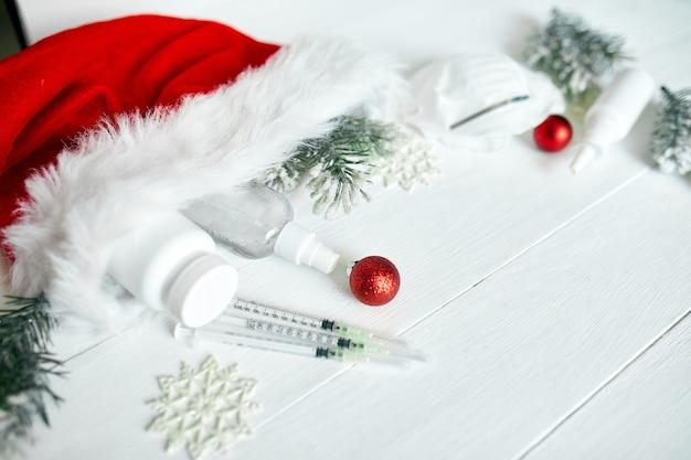 Piatto di coronavirus medico di natale, maschera protettiva, pillole, antisettici, decorazione su sfondo bianco, tema del nuovo anno vista dall'alto, minimalismo, layout piatto, concetto di covid e felice anno nuovo