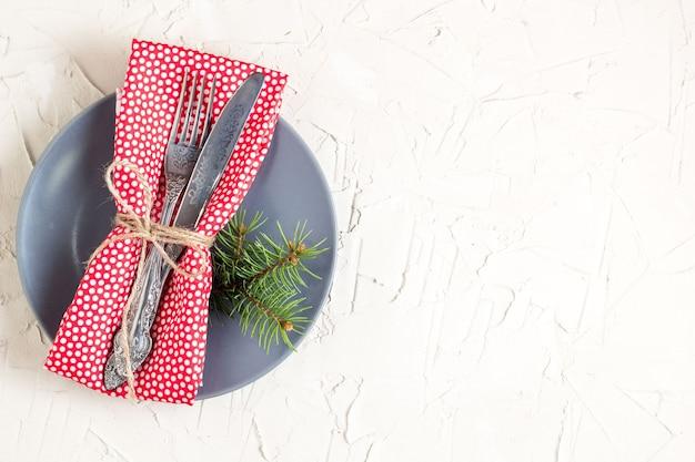 Sfondo del menu di natale con tovagliolo coltello forchetta e brunch albero di abete sulla tavola bianca.
