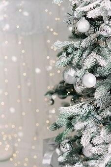Fondo minimo di natale, un albero di natale decorato con palline su uno sfondo di luci bokeh sfocate