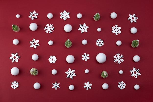 Natale il concetto minimo. palle di neve e fiocchi di neve su sfondo rosso.