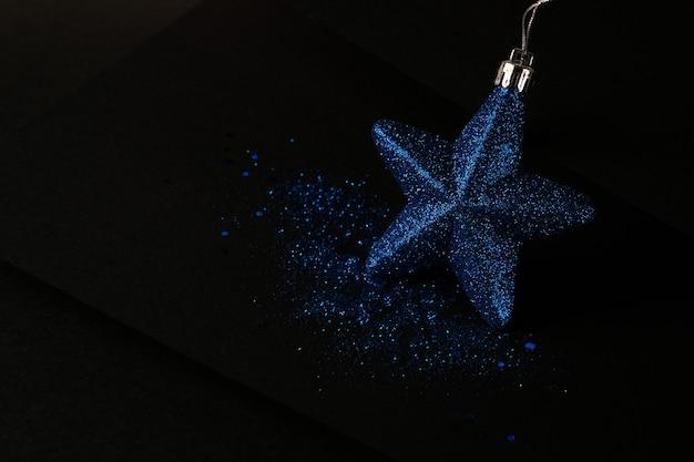 Composizione natalizia minimalista e semplice in colore nero opaco. regali di natale, decorazioni su sfondo nero. vista piana laico e superiore con lo spazio della copia