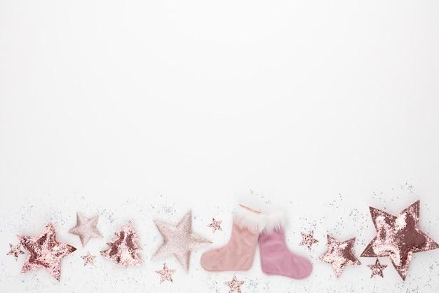Composizione minimalista e semplice di natale in colore rosa. stella di natale, decorazioni su sfondo bianco. vista piana laico e superiore con lo spazio della copia