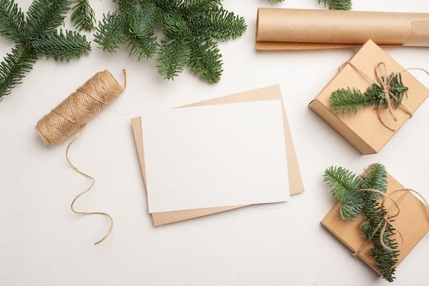 Cartolina d'auguri di mockup di natale con busta su fondo bianco in legno con rami di abete e felice anno nuovo.