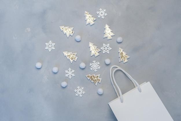Concetto di acquisto di mockup di natale. pacchetto bianco kraft con fiocchi di neve e abete con posto per il testo.
