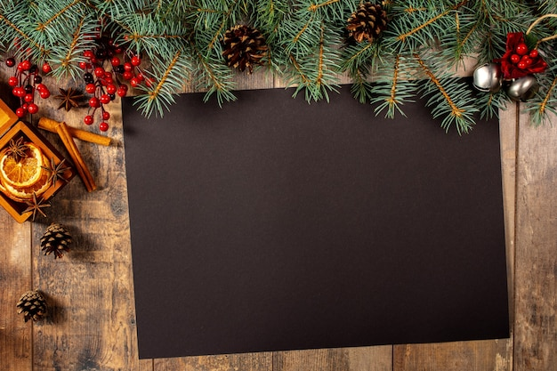 Mockup di natale con foglio di carta nero con decorazioni natalizie su un tavolo di legno scuro