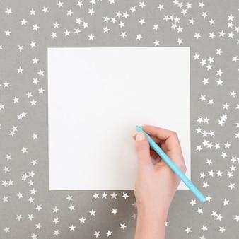 Mockup di natale con stelle di coriandoli d'argento su sfondo grigio. la mano di una donna scrive un elenco.