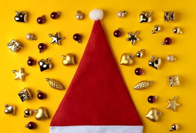 Composizione moderna di natale. decorazioni dorate e cappello da babbo natale su sfondo giallo.