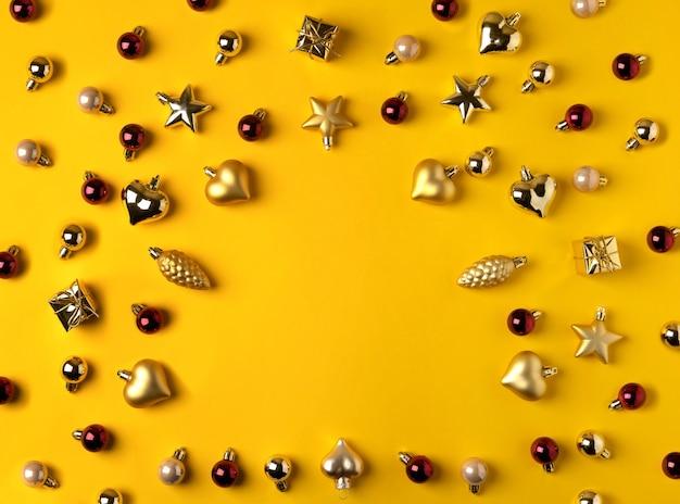 Composizione moderna di natale. decorazioni dorate su sfondo giallo.