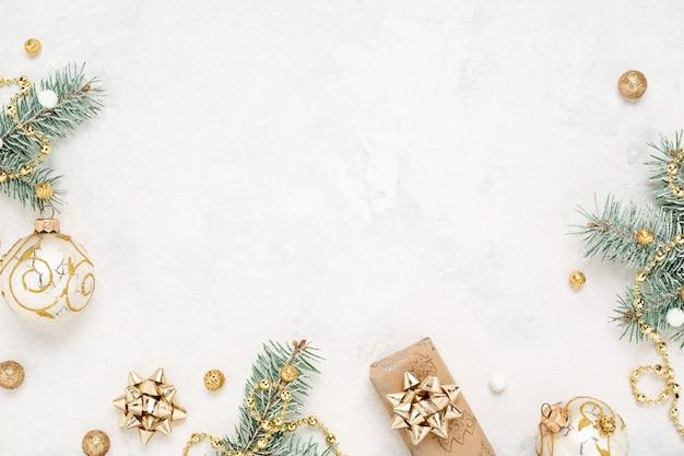 Bordo di umore natalizio di decorazioni regalo, verde e oro su sfondo bianco.