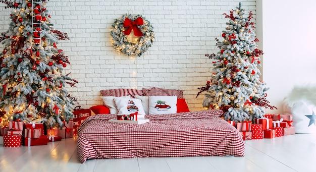 Atmosfera natalizia. interiore di natale di una camera da letto. decorazioni di capodanno e albero di natale con regali in un appartamento moderno.