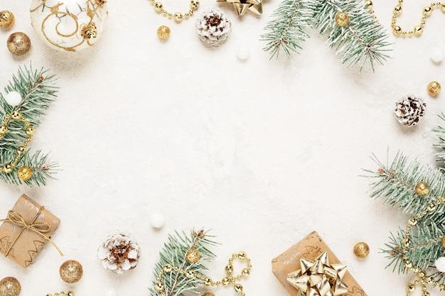 Cornice d'atmosfera natalizia di regali, abete rosso e decorazioni in oro su uno spazio bianco.
