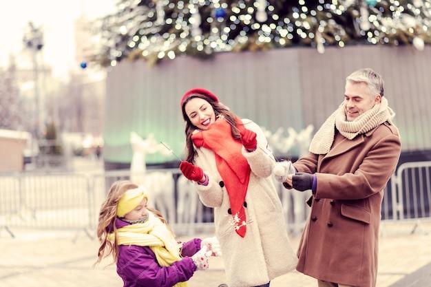 Atmosfera natalizia. gente felice positiva che cammina vicino all'albero di natale e posa sulla macchina fotografica