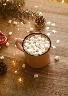 Foto lunatica di natale con una tazza di caffè rosa con marshmallow e coriandoli
