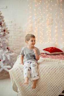 La mattina di natale ragazzo seduto sul letto