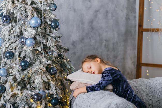 Mattina di natale. bambina stanca che dorme sul divano, aspettando babbo natale con doni in abete decorato a casa.