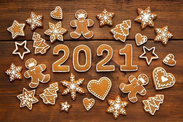 Mosaico di natale biscotti di panpepato fatti in casa a forma di un uomo mascherato e numeri del nuovo anno su tavola di legno marrone, vista dall'alto