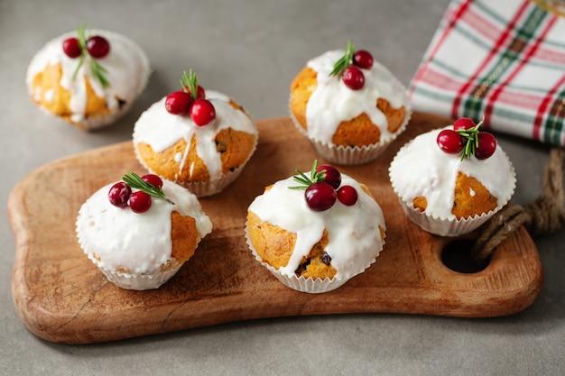 Muffin di natale con mirtilli rossi e rosmarino serviti su tavola di legno.