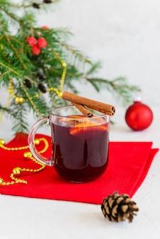 Vin brulè di natale con cannella, anice, chiodi di garofano e arancia in una tazza con un albero di natale.