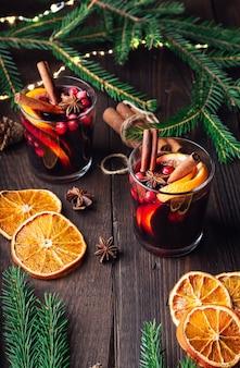 Vin brulé di natale con arancia di mirtilli rossi e spezie su fondo di legno rustico